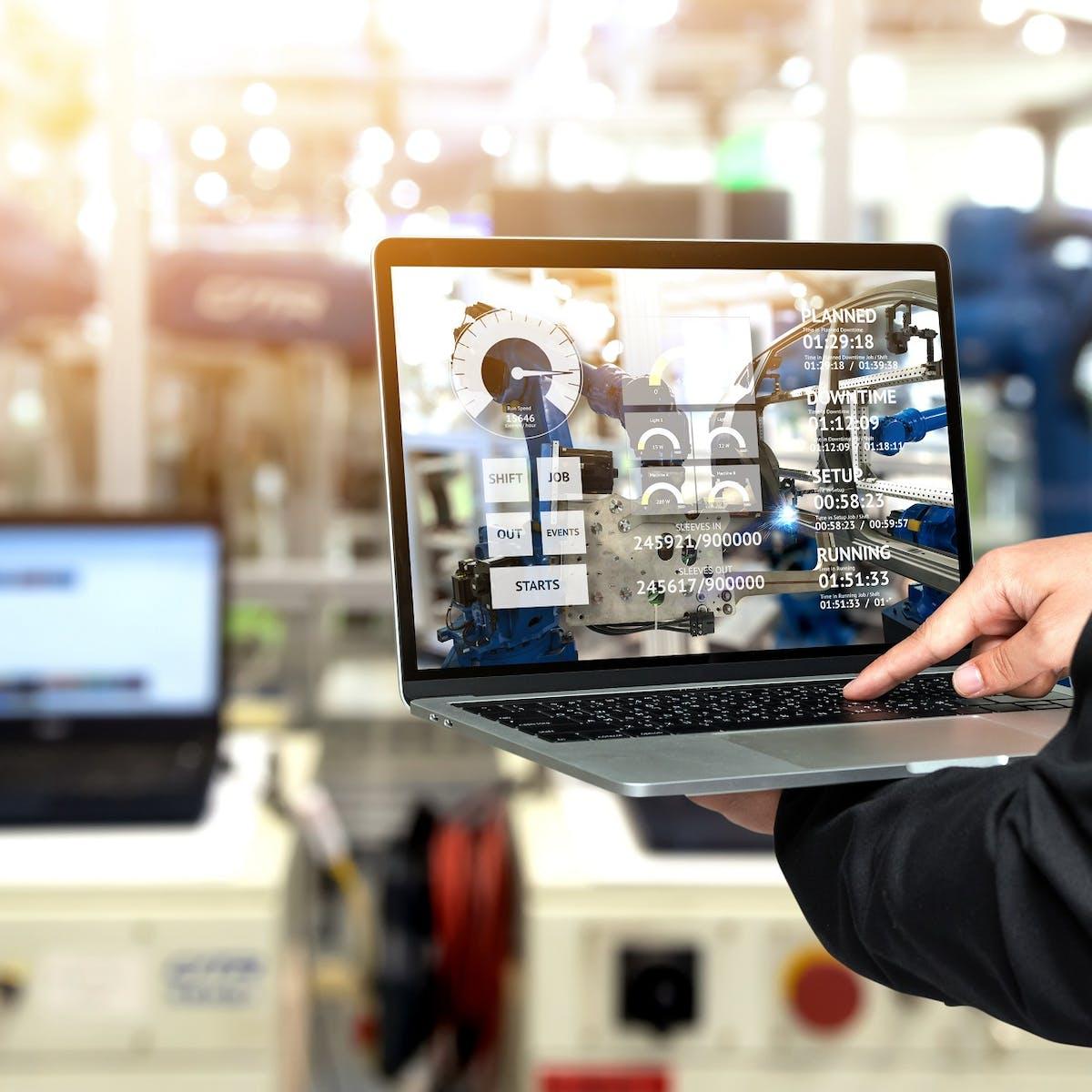Werker hält Laptop mit Maschinendaten in der Hand